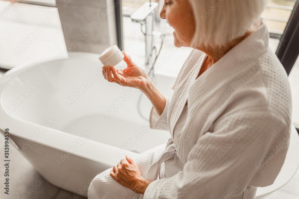 Fototapeta Smiling senior lady holding jar of cream