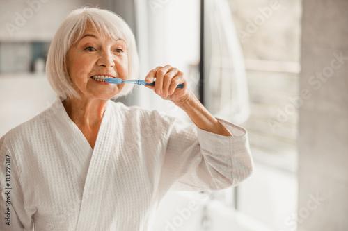 Fototapeta Elderly woman in bathrobe brushing teeth in the morning