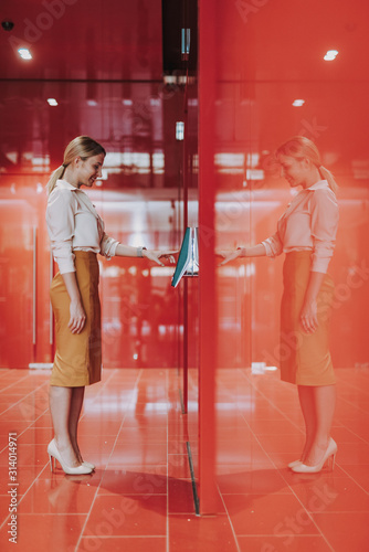 Stylish young woman entering access code and smiling Wallpaper Mural
