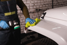Master In A Jumpsuit Wipes The Car's Wing With A Yellow Rag Before Polishing
