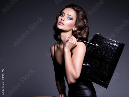 Photo Beautiful woman with brown hair holds black handbag