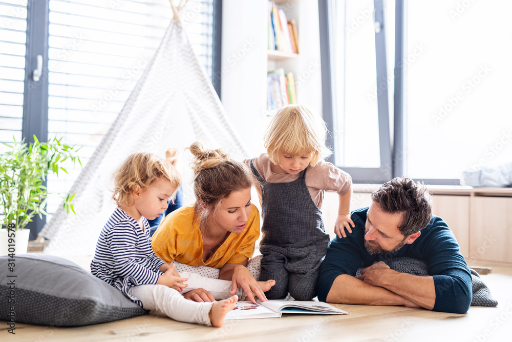 Fototapeta Young family with two small children indoors in bedroom reading a book.