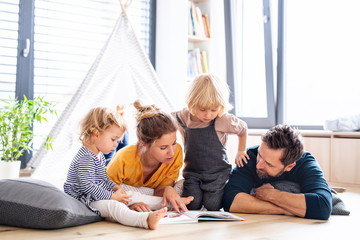FototapetaYoung family with two small children indoors in bedroom reading a book.