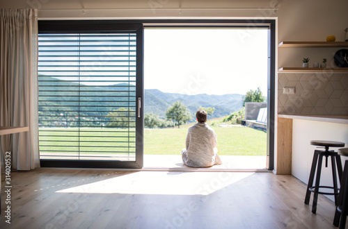 Rear view of young woman sitting by patio door at home. Copy space.