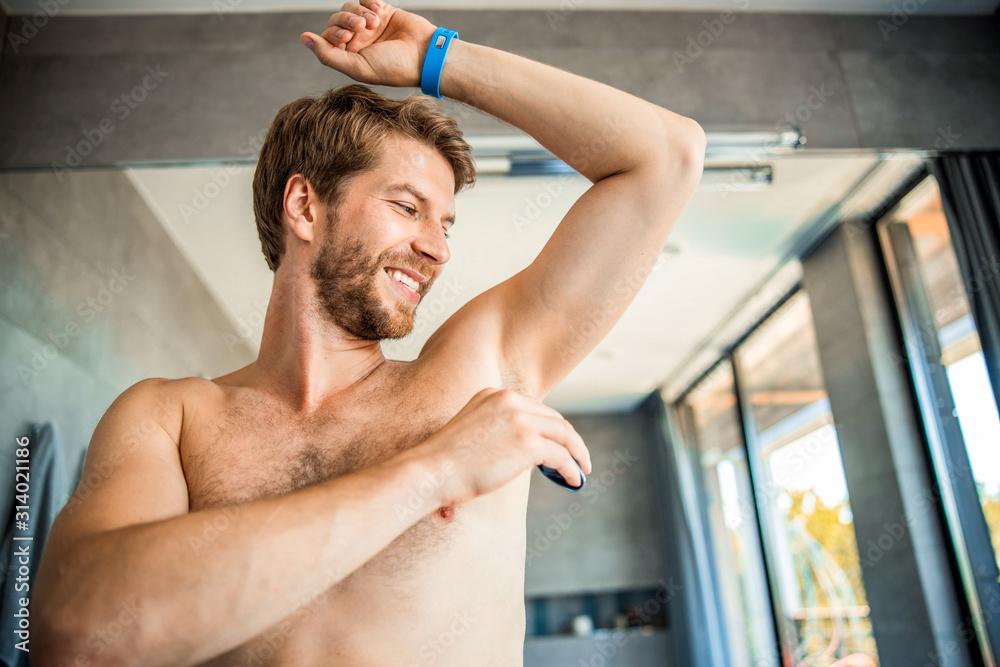 Fototapeta Joyful young man protecting skin from perspiring