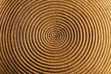 Background Of A Spiral Woven Wicker Texture - Detail Of A Brown And Orange Basket