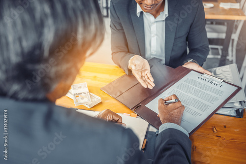 Businessman puts signature on contract at business meeting and passing money aft Wallpaper Mural