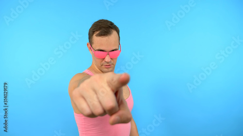 Photo crazy man in pink glasses come here gesture on blue background