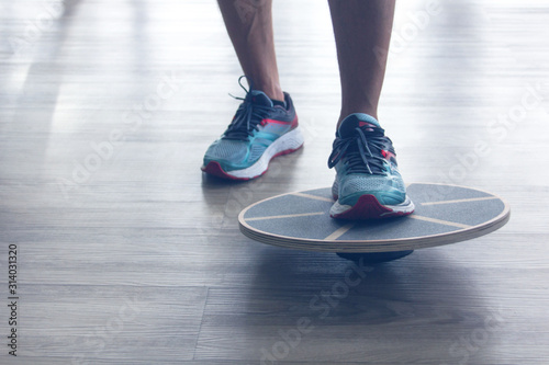 Photo Mans legs in trainers testes balance board with one leg.