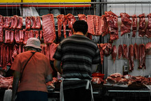 Butcher And Customer Buying And Selling Meat On Street Market Store In Hong Kong
