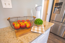 Fruit Basket With Red Apples On Top Of Chopping Board And Marble Countertop