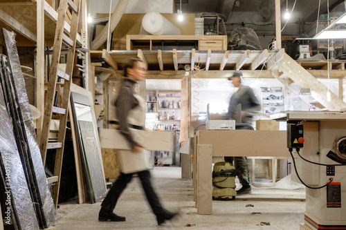 Exposure photography two unidentified young employees of small woodworking and furniture industry working on new furniture collection Fototapet