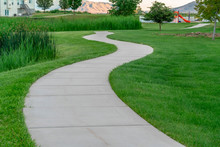 Narrow Paved Pathway Winding Through Lush Green Grasses Of Park With Playground