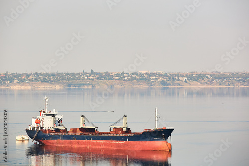Empty bulk carrier cargo ship with deck cranes sailing on a river calm water Canvas Print