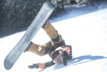 転倒する女性スノーボ...