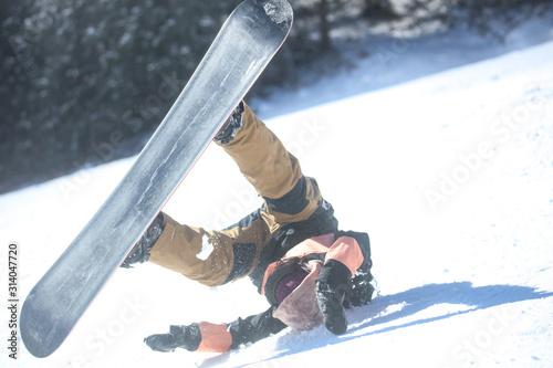 転倒する女性スノーボーダー Fotobehang