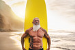 Leinwandbild Motiv Happy fit senior having fun surfing at sunset time - Sporty bearded man training with surfboard on the beach - Elderly healthy people lifestyle and extreme sport concept