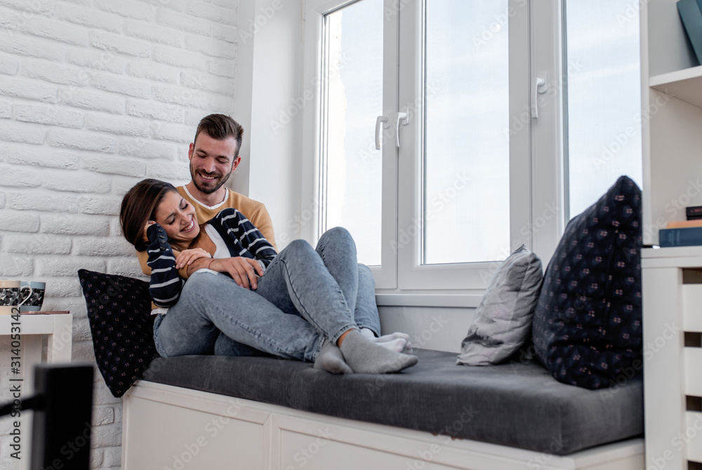 Fototapeta Young couple in love enjoying time together at home sitting by the window and relaxing in apartment.
