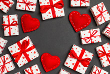 Top View Of Festive Gift Boxes And Red Textile Hearts On Colorful Background With Copy Space. St Valentine's Day Concept
