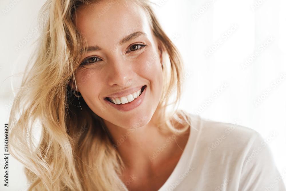 Fototapeta Smiling young beautiful blonde woman wearing t-shirt