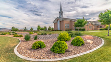 Pano Scenic View Of Church With White Steeple And Landscaped Yard On A Cloudy Day