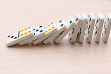 White Dominoes Stand In A Row On A Light Surface And Fall, Close-up
