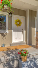 Vertical Frame Outdoor Stairs Porch And White Front Door With Wreath At The Facade Of A Home