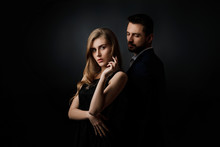 Elegant Couple On Black Background. Handsome Man And Beautiful Woman In Black Dress