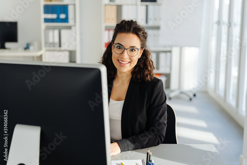 Young businesswoman sitting working at a desktop Fototapet