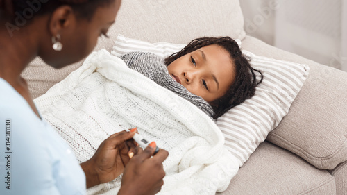 Canvas Print Afro mom checking temperature of her ill daughter