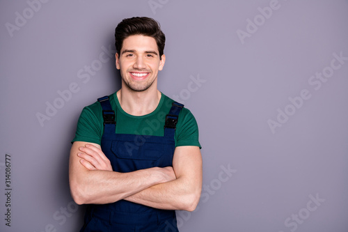 Photo of handsome virile muscles guy hold arms crossed self-confident best manual worker skilled engineer wear green t-shirt blue safety dungarees isolated grey background - 314086777