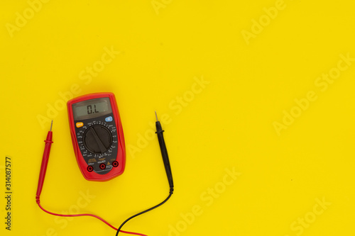 Tela  Top view multimeter on yellow background with measuring tips