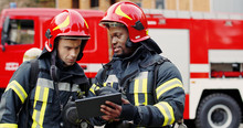 Portrait Of Two Firefighters In Fire Fighting Operation, Fireman In Protective Clothing And Helmet Using Tablet Computer In Action Fighting.