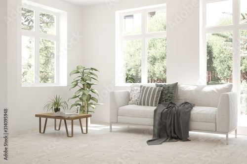Obraz na plátně Stylish room in white color with sofa and summer landscape in window