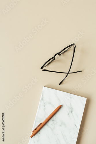 Marble styled notebook, pen, glasses on pastel beige background. Minimalist home office desk table. Flat lay, top view woman lifestyle business concept.