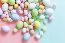 Happy Easter Concept. Easter Candy Chocolate Eggs And Jellybean Sweets Isolated On Trendy Pastel Blue Pink Background. Simple Minimalism Flat Lay Top View Copy Space