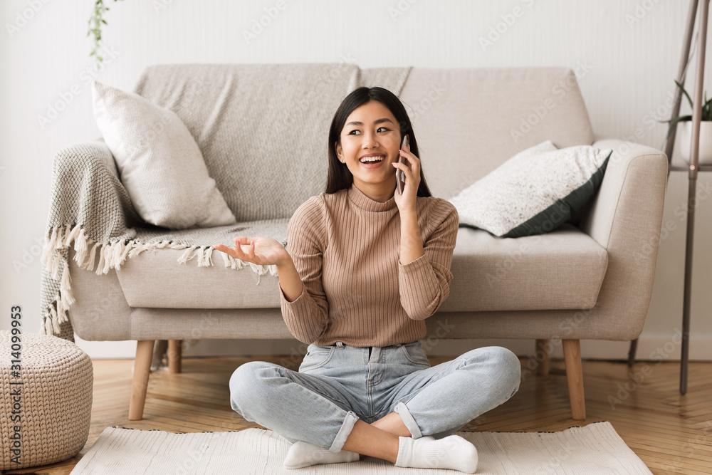 Fototapeta Overjoyed asian girl talking on cellphone with friend