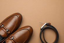 Pair Of Stylish Male Shoes And Leather Belt On Brown Background, Flat Lay