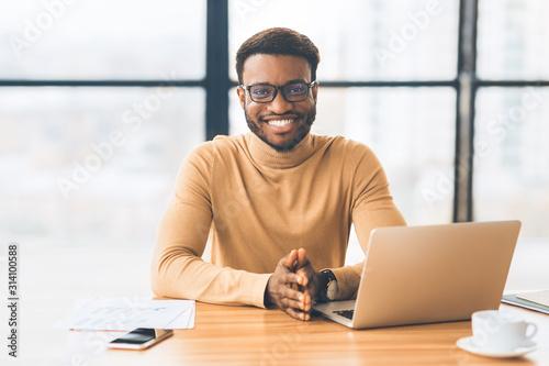 Fototapeta Smiling black businessman working at modern office obraz
