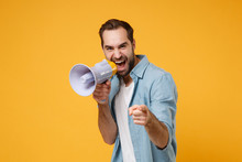 Funny Young Man In Casual Blue Shirt Posing Isolated On Yellow Orange Background Studio Portrait. People Lifestyle Concept. Mock Up Copy Space. Screaming In Megaphone Pointing Index Finger On Camera.