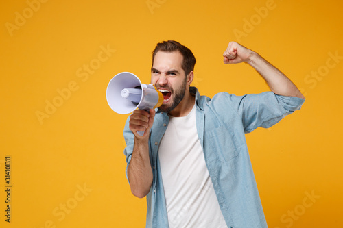 Fototapety, obrazy: Crazy young man in casual blue shirt posing isolated on yellow orange background, studio portrait. People sincere emotions lifestyle concept. Mock up copy space. Scream in megaphone clenching fist.