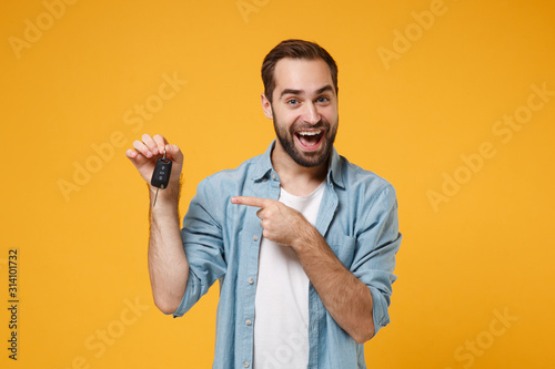 Fotomural Excited young man in casual blue shirt posing isolated on yellow orange background, studio portrait