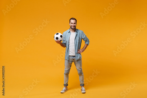 Photo Smiling young bearded man in casual blue shirt posing isolated on yellow orange wall background, studio portrait
