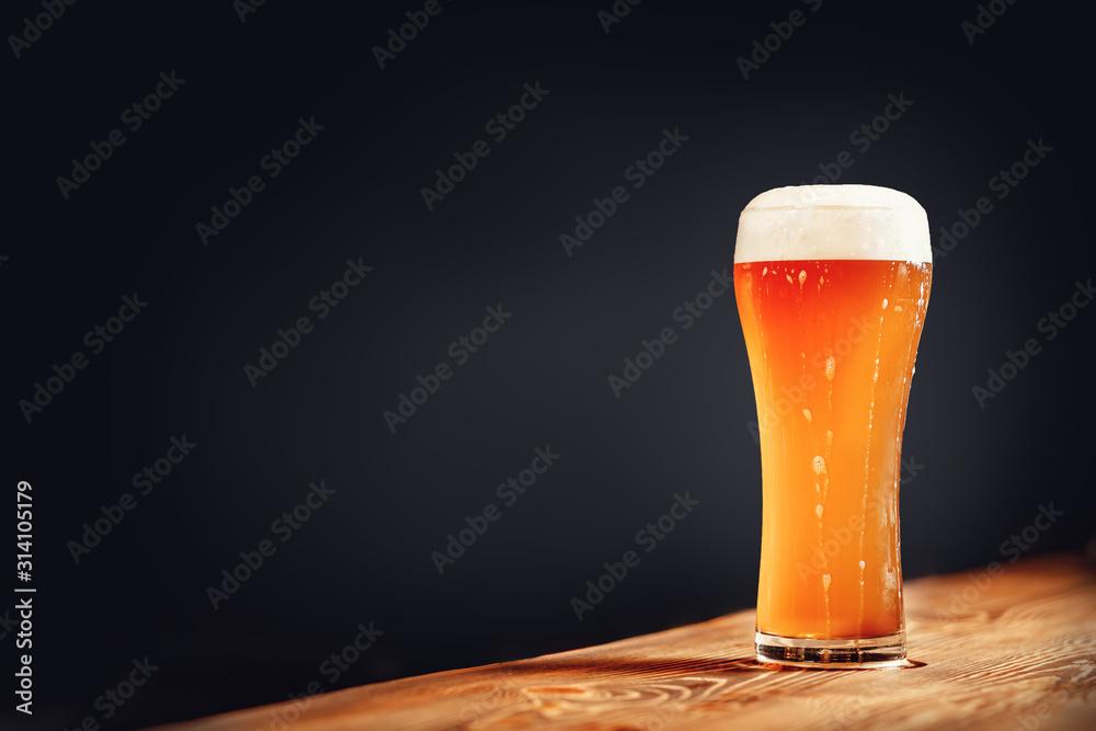 Fototapeta Long glass of fresh light beer with foam on wooden bar counter, dark background