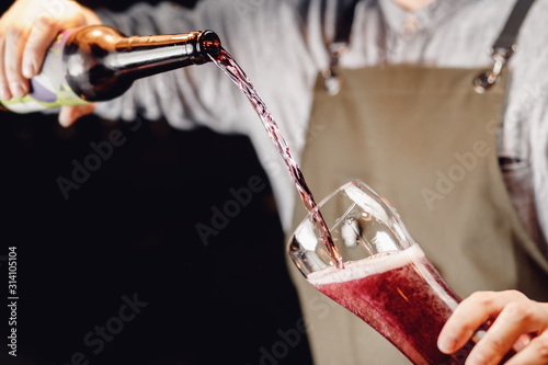 Barman pours craft blueberry cherry beer from bottle into glass, dark background Canvas Print