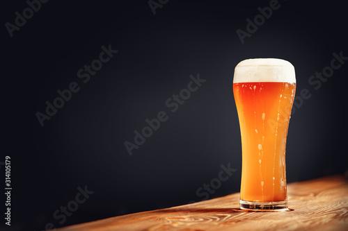 Fototapeta Long glass of fresh light beer with foam on wooden bar counter, dark background obraz