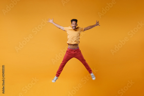 Fotografie, Obraz Funny young african american guy in bright casual clothes posing isolated on yellow orange background studio portrait
