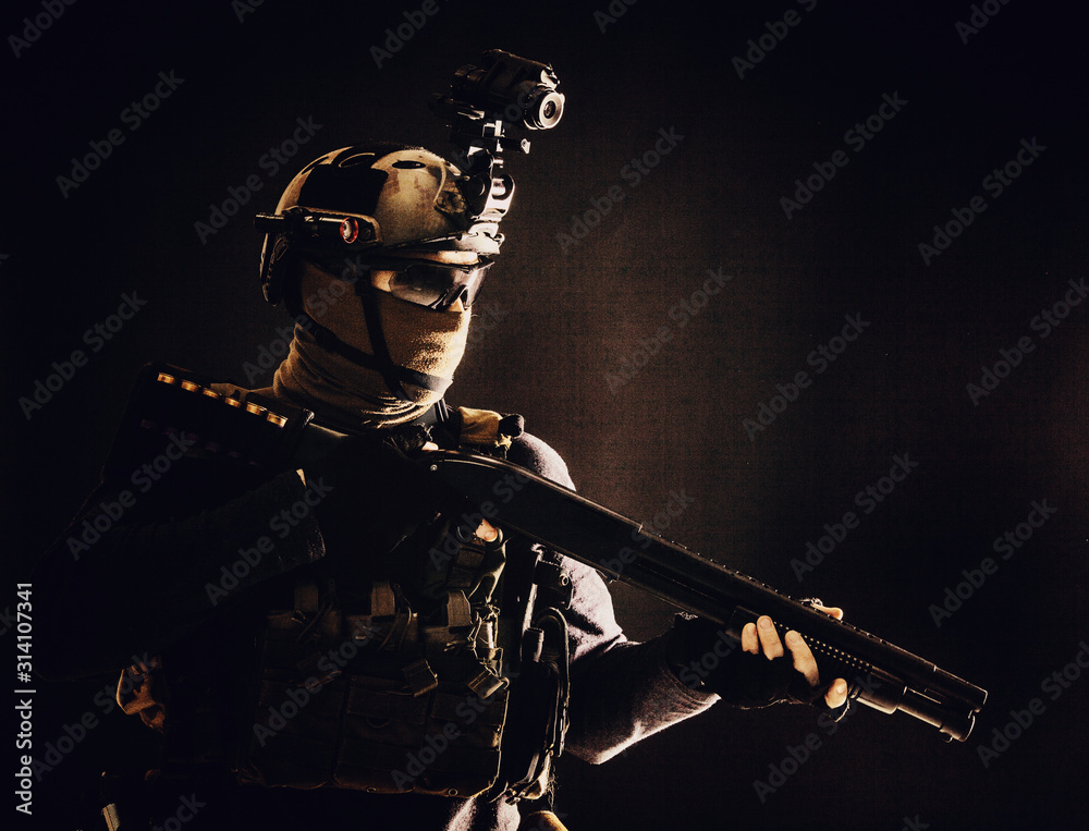 Fototapeta Shoulder portrait of army elite troops soldier, anti-terrorist tactical team wit shotgun, helmet with thermal imager, hiding face behind mask, armed rifle with optical scope, studio shoot on black