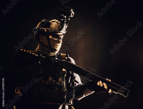 Obraz Shoulder portrait of army elite troops soldier, anti-terrorist tactical team wit shotgun, helmet with thermal imager, hiding face behind mask, armed rifle with optical scope, studio shoot on black - fototapety do salonu