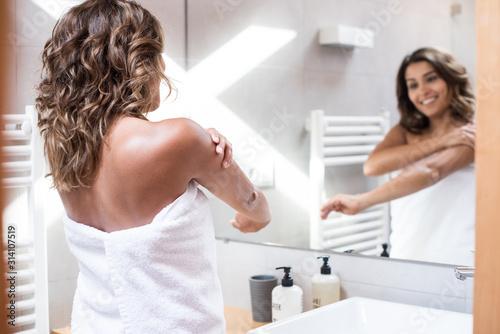 Woman applying body lotion Canvas Print